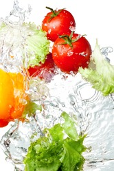Three Fresh red Tomatoes, Yellow Bell Pepper and lettuce in splash water Isolated on white background
