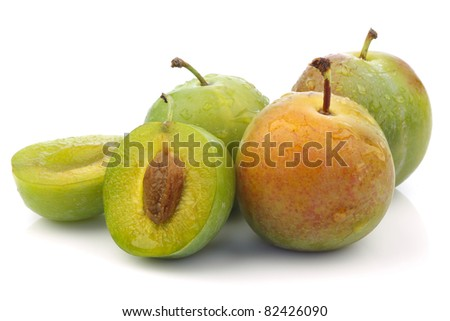"three fresh ""Reine Claude""plums and a cut one  on a white background"