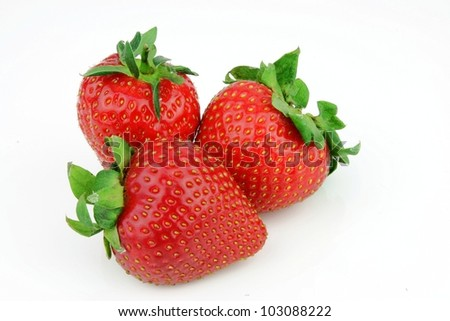 Three Fresh strawberries piled together.