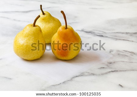 Three fresh yellow pears with pink blush, on a white marble counter top.  The pears are sitting on a square of white tulle netting.