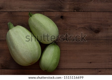 Three  fresh zucchini on a wooden background. Harvest season themes #1515116699