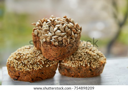 Three freshly baked raisins cakes with sesame and sunflower seeds isolated on gray wooden table. Three muffins on blurred nature background. Close up view #754898209