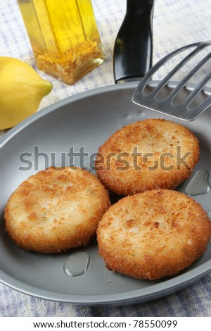 three freshly fried fish cakes in a pan