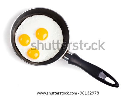 three fried egg on pan without oil isolated on white