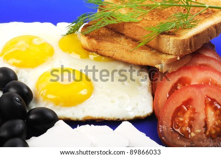 Three fried eggs , olive, cheese and toast on a blue plate - stock photo