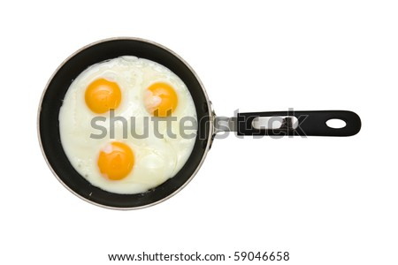 three fried unbroken eggs on black non-stick frying pan; shot from the top; isolated