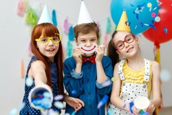 Three friendly children in festive cone caps and big eyewear, stand in decorative room with balloons, have fun together as celebrate birthday look with happy expressions at camera, enjoy playing games