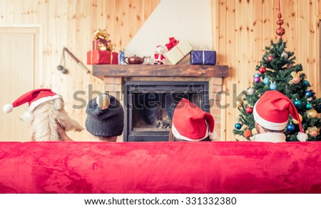 Three friends and a dog sitting on the couch in front of the fireplace. Concept about holidays and christmas