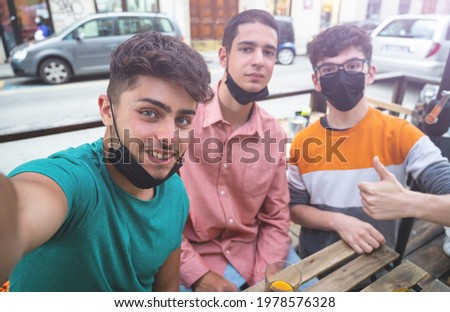 Three friends are drinking at an outing after the coronavirus lockdown. They take a group selfie. Concept of friendship, new normal, pandemic fight. Focus on the boy on the left. Cold light filter. Stock foto ©