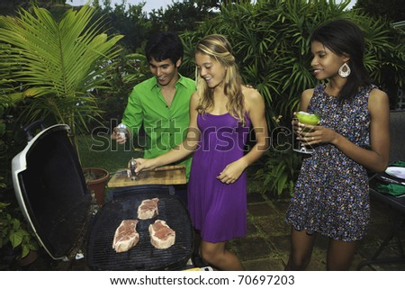 three friends at a barbecue party in their tropical garden in hawaii