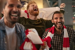 Three friends cheering for england sports team. Football fans wearing poland flag and scarf with painted face celebrating victory in bar. Group of young men shouting excitingly for soccer team.
