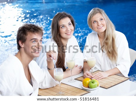 Three friends drink cocktails and cafe at pool
