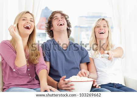 Three friends eating popcorn while laughing at the show while they sit on the couch together