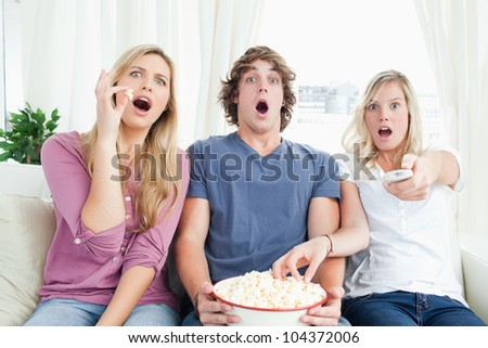 Three friends enjoying popcorn together while getting scared by the tv show