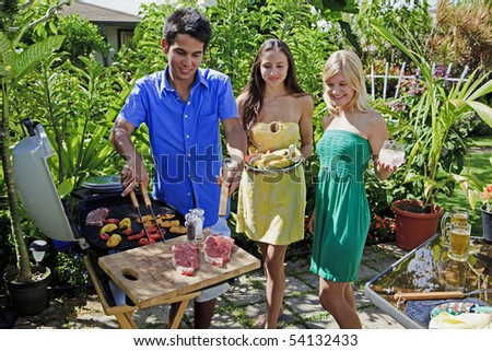 three friends having a barbecue lunch in their tropical garden