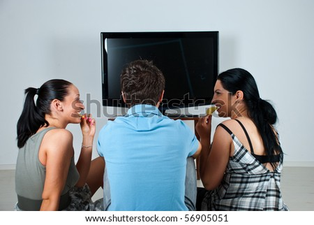 Three friends having a  funny conversation while watching soccer game at tv and eating chips - stock photo