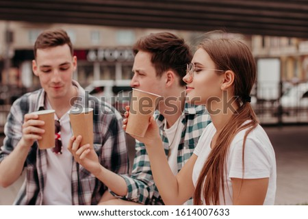 Three Friends Having Hot Drinks outdoors In Plastic Cups Outdoor. The Girl Is Smelling The Drink And Wearing Glasses. They Ae Under The Bridge.