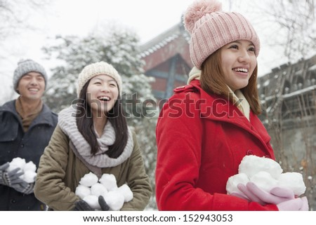 Three friends Holding snow balls in snow in park