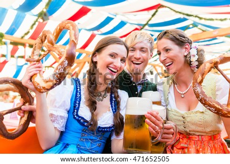 Three friends in beer tent at Dult or Oktoberfest holding giant pretzels up in the air Photo stock ©
