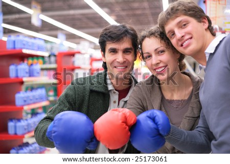 Three friends in boxing gloves in shop