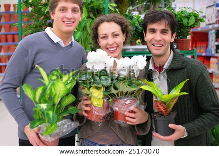 Three friends in shop holds pots with plants in shop, focus on woman - stock photo