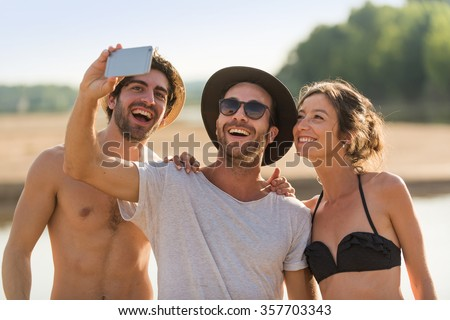 Three friends in their 30's taking selfies at the beach. A woman wearing a bikini and two men with hats and sunglasses are having fun with a smartphone. They are looking at the screen for the picture.