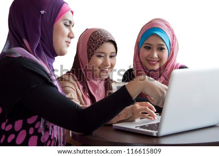 three friends laughing at content on a laptop