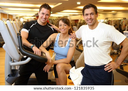 Three friends (2 men and 1 woman) in a gym on a exercising bike - stock photo