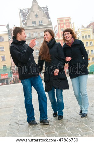 Three friends on a street in old city - stock photo