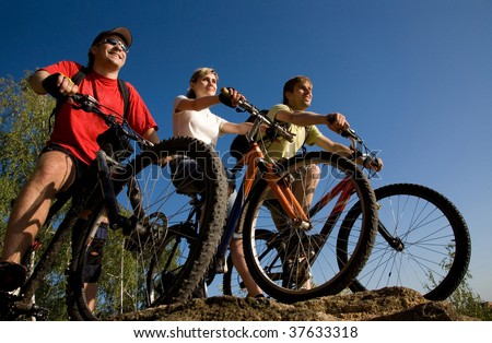Three friends on bicycles on the brink of a rock and look afar from rock breakage