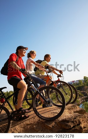 Three friends on bicycles on the brink of a rock and look afar from rock breakage - stock photo