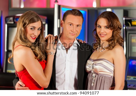 Three friends - one man and two women - in Casino in a playful mood