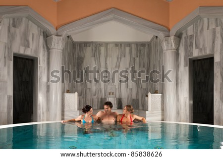 Three friends - one man and two women - in swimming pool or thermal bath doing wellness