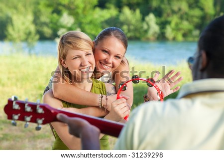 three friends playing guitar and tambourine outdoors.