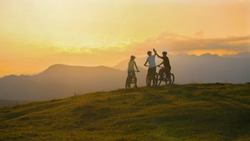 Three friends ride their electric bicycles up to the edge of a grassy hill and high five at sunset. Mountain bikers celebrate at sunset after a successful mountain biking journey in scenic Slovenia.