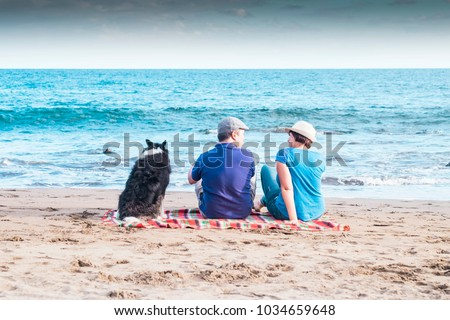 three friends sit down looking at the ocean enjoying the beach and the vacation. Relationship and friendship concpet between middle aged humans and nice dog.