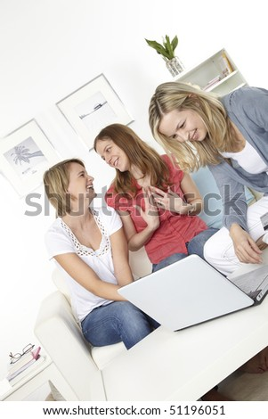 three friends sit on a white sofa and make an online shopping