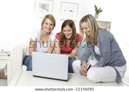 three friends sit on a white sofa and make an online shopping - stock photo
