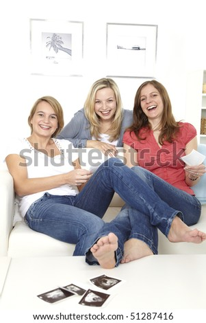 three friends sit on sofa and have a look at ultrasonograms