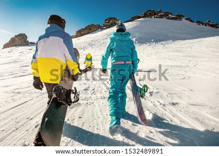 Three friends snowboarders goes uphill with snowboards in hands for backcountry or free ride. Ski tour concept with group of peoples #1532489891