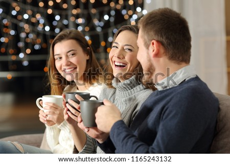 Three friends talking and laughing in the night sitting on a couch in the living room at home