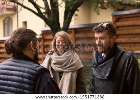 Three friends, two guys and a girl met on the street in the autumn and are having fun talking. One guy smokes a cigarette. Concept of communication and news story.