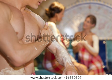 Three friends - two women, one man - doing wellness in the sauna of a thermal bath; close-up of the man in front