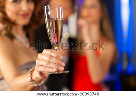 Three friends with champagne in a bar, a woman is looking in the camera; focus on glass in front