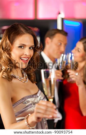 Three friends with champagne in a bar or casino, a woman is looking in the camera