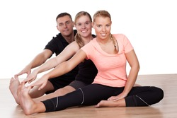 Three friends working out in a gym sitting on the wooden floor doing stretching exercises with their legs extended