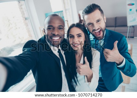 Photo of Three funny, cheerful friends having free time,  showing like symbol,  man shooting selfie on front camera of smart phone, together standing in workplace, workstation