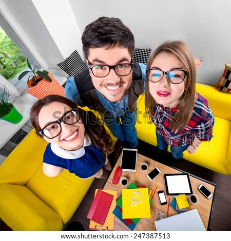 Three funny nerds looking together at camera standing in the room with couch and different digital stuff on background