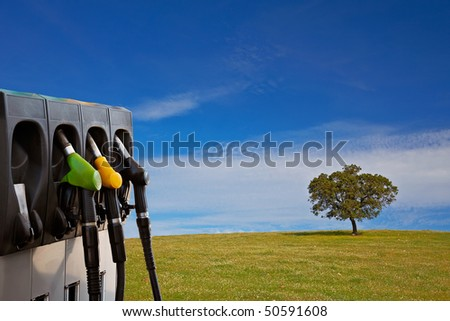 Three gas pump nozzles over a nature background with solitary tree