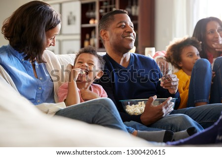Three generation African American family family sitting on the sofa in living room, watching TV and eating popcorn, selective focus